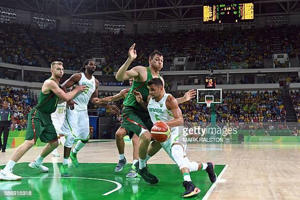Brazil's point guard Raulzinho Neto works around Lithuania's small forward Jonas Maciulis during a Men's round Group B basketball match between...