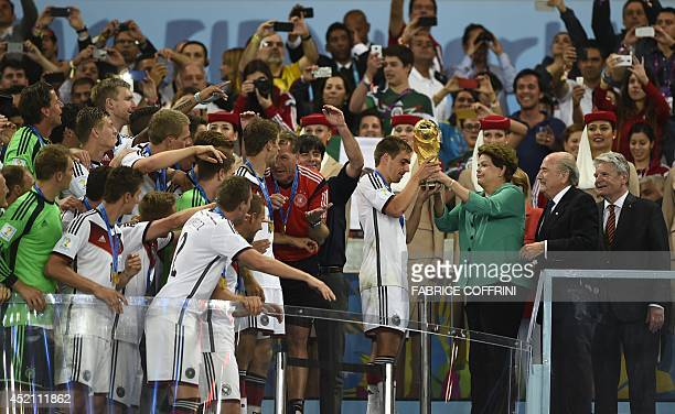 Brazil's President Dilma Roussef presents the World Cup trophy to Germany's defender and captain Philipp Lahm after Germany won the 2014 FIFA World...