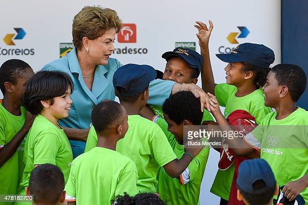 Brazil's President Dilma Rousseff is greeted by children during the Olympic Day celebration and presentation of Brazilian national teams mascot Ginga...