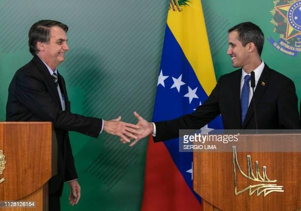 Brazil's President Jair Bolsonaro and Venezuelan opposition leader and self-declared acting president Juan Guaido shake hands during a joint press...