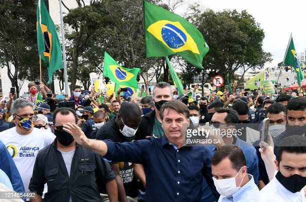 Brazil's President Jair Bolsonaro greets supporters upon arrival at Planalto Palace in Brasilia, on May 24 amid the COVID-19 coronavirus pandemic. -...