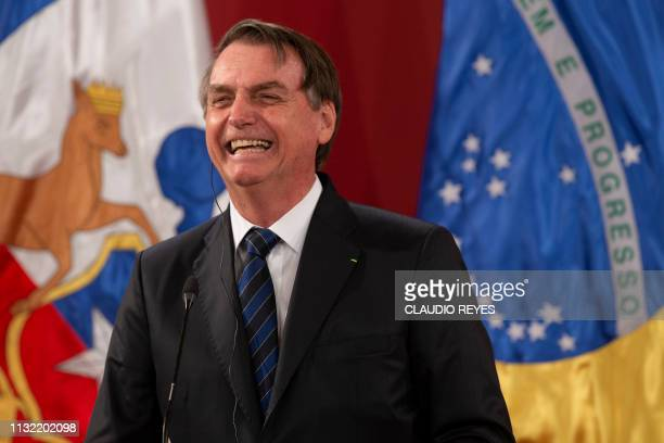 Brazil's President Jair Bolsonaro laughs during a joint press conference with Chilean President Sebastian Pinera at La Moneda Presidential Palace in...