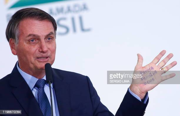 """Brazil's President Jair Bolsonaro shows written on the palm of his hand """" Homeland, Family, God """" during a ceremony to mark his 400 days in office at..."""