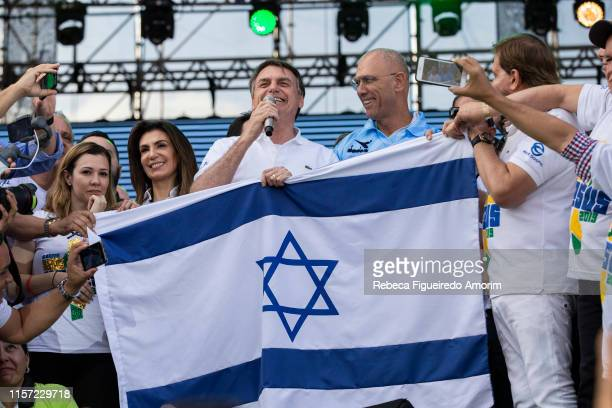 Brazil's President Jair Messias Bolsonaro speaks alongside of Israel's ambassador Yossi Shelley during their participation at March for Jesus on June...