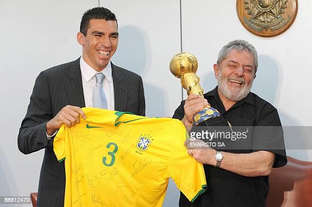 Brazil's President Luiz Inacio Lula da Silva and footballer Lucio pose with a Brazilian soccer team jersey autographed by the team and the...