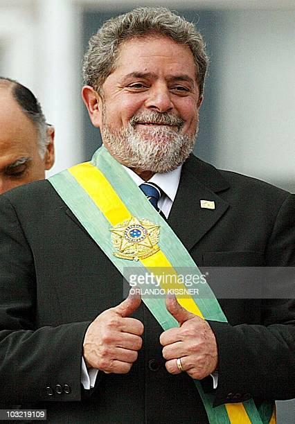 Brazil's President Luiz Inacio Lula da Silva celebrates after receiving the presidential band from outgoing President Fernando Henrique Cardoso at...
