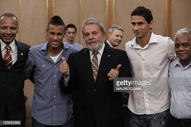Brazil's President Luiz Inacio Lula da Silva gestures next to Santos FC player Neymar his father also named Neymar also Santos FC player Paulo...
