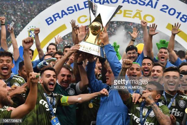 Brazil's President-elect, Jair Bolsonaro and Palmeiras' coach Luiz Felipe Scolari lift the trophy as they celebrates with Palmeiras' players after...