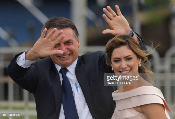Brazil's Presidentelect Jair Bolsonaro gestures next to his wife Michelle Bolsonaro as the presidential convoy heads to the National Congress for his...