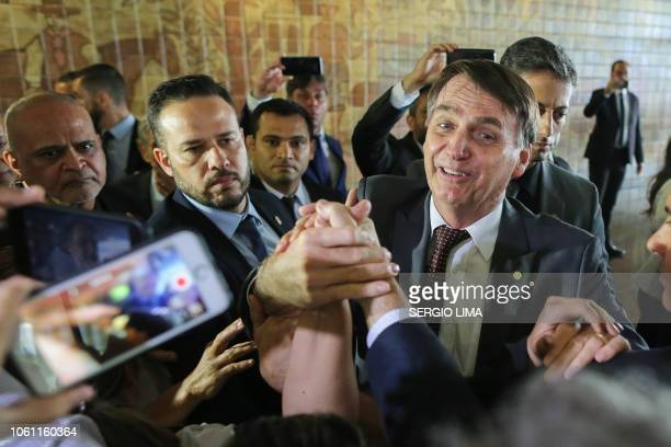 Brazil's Presidentelect Jair Bolsonaro greets people during his visit to the Superior Court of Labour in Brasilia on November 13 2018 Bolsonaro who...