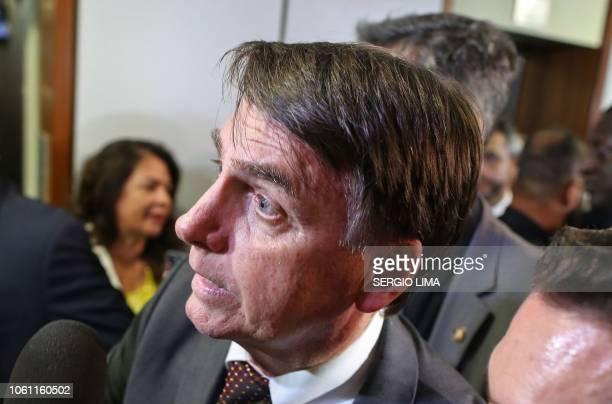 Brazil's Presidentelect Jair Bolsonaro greets people during his visit to the Superior Court of Labour in Brasilia on November 13 2018 Bolsonaro who...
