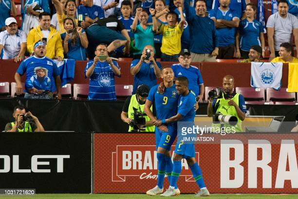 Brazil's Richarlison celebrates his goal with teammate Douglas Costa against El Salvador during an international friendly at FedEx Field in Landover...