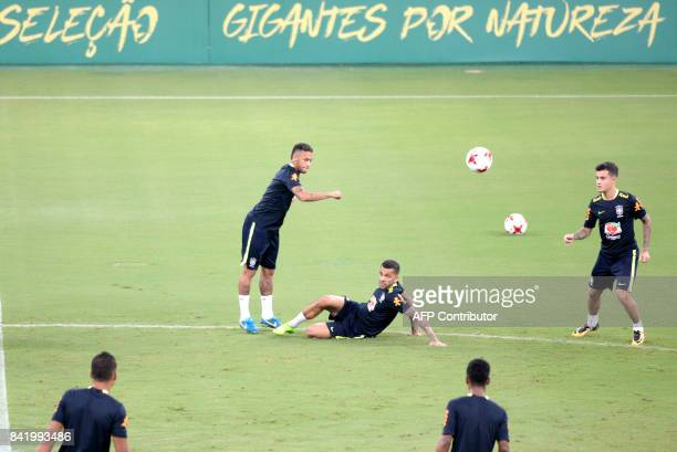 Brazil's right back Daniel Alves vies for the ball with Neymar observed by midfielder Philippe Coutinho during a training session in Arena Amazonia...