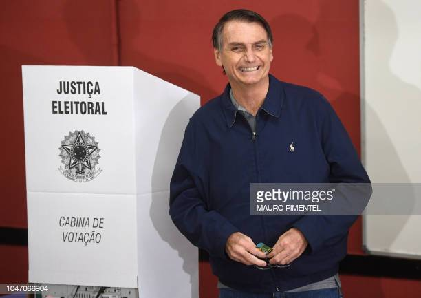 TOPSHOT Brazil's rightwing presidential candidate for the Social Liberal Party Jair Bolsonaro smiles after casting his vote during general elections...