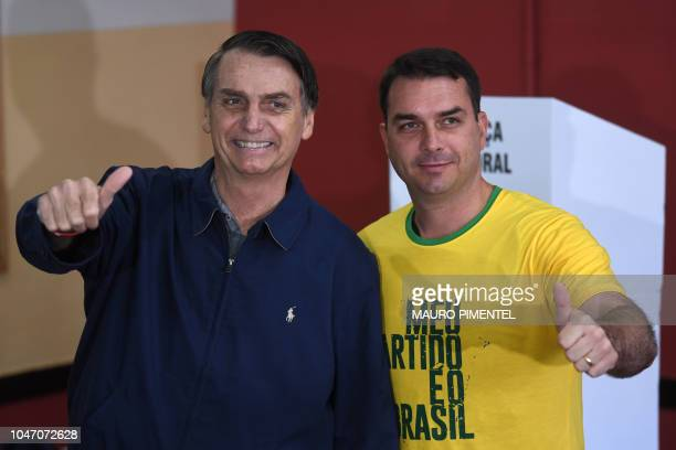 Brazil's rightwing presidential candidate for the Social Liberal Party Jair Bolsonaro poses with his son and senate candidate Flavio after casting...
