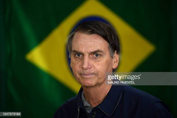 TOPSHOT Brazil's rightwing presidential candidate for the Social Liberal Party Jair Bolsonaro walks in front of the Brazilian flag as he prepares to...
