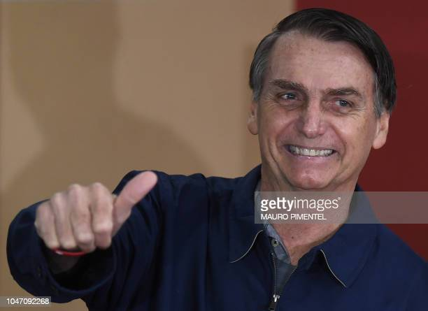 Brazil's rightwing presidential candidate for the Social Liberal Party Jair Bolsonaro gives his thumb up after casting his vote during the general...