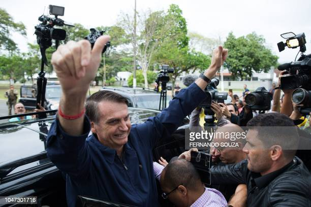 Brazil's rightwing presidential candidate for the Social Liberal Party Jair Bolsonaro gives his thumbs up after casting his vote at Villa Militar...