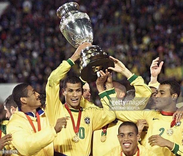 Brazil's Rivaldo holds the Copa America trophy 18 July as he celebrates with teammates after they defeated Uruguay 30 in Asuncion Rivaldo scored two...