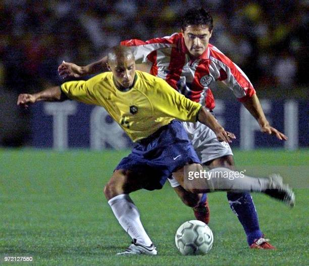 Brazil's Roberto Carlos fights for the ball with Paraguay's Roberto Acuna 15 August in their KoreaJapan 2002 World Cup qualification match in Porto...