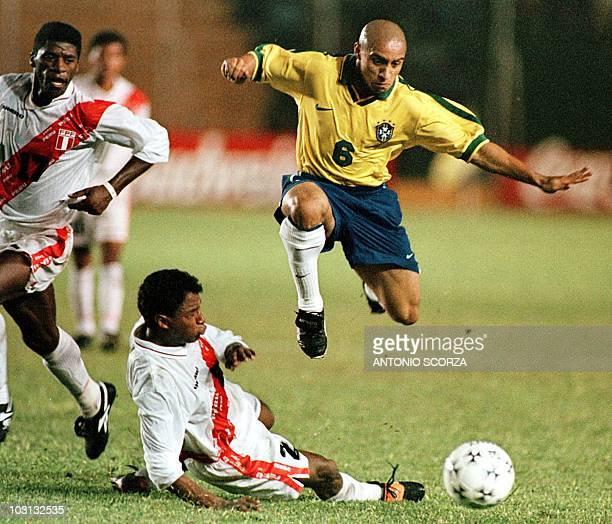 Brazil's Roberto Carlos takes the ball from Peru's Jose Reyna and Eddy Carazas 26 June during the semi-final Copa America at Tahuchi Aguilera Stadium...