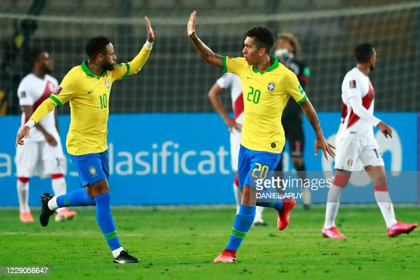 Brazil's Roberto Firmino celebrates with teammate Neymar after teammate Richarlison pushed his header into the goal to score against Peru during...