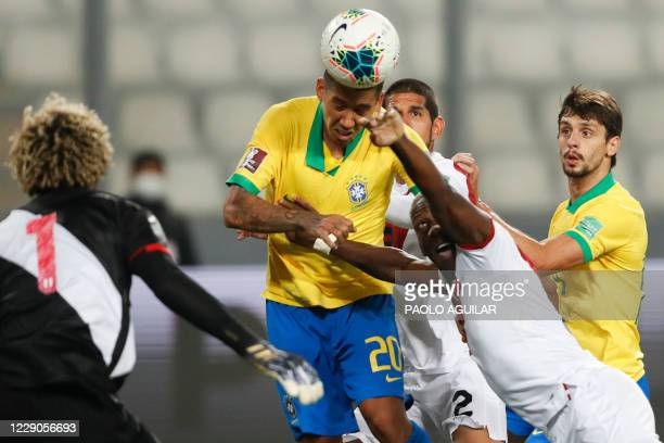 Brazil's Roberto Firmino heads the ball next to Peru's Luis Advincula for teammate Richarlison to push it into the goal to score against Peru during...