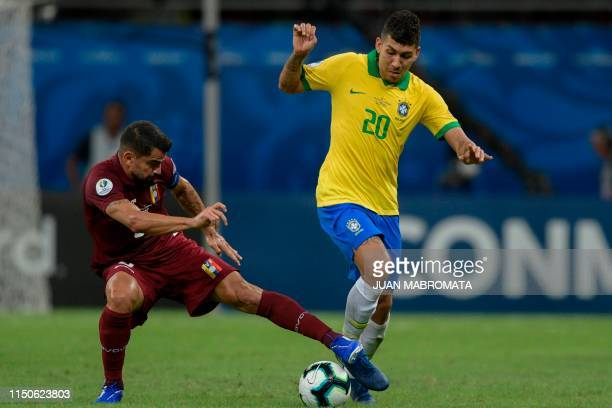 Brazil's Roberto Firmino is marked by Venezuela's Tomas Rincon during their Copa America football tournament group match at the Fonte Nova Arena in...
