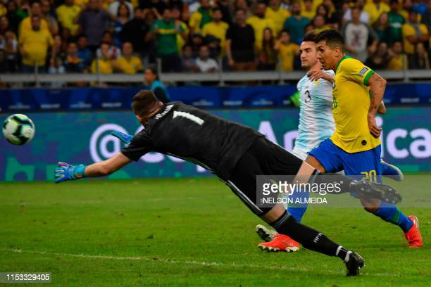 Brazil's Roberto Firmino scores past Argentina's goalkeeper Franco Armani during their Copa America football tournament semifinal match at the...