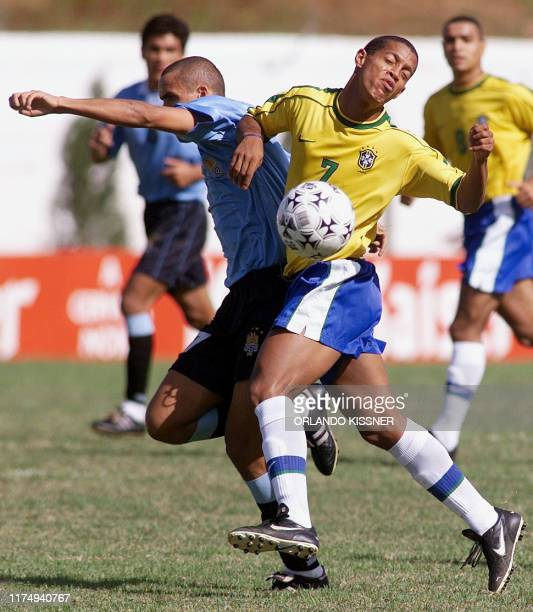 Brazil's Ronaldinho Gaucho battles for the ball against Uruguay's Christian Callejas 06 February 2000 in Londrina Brazil for a chance to compete in...