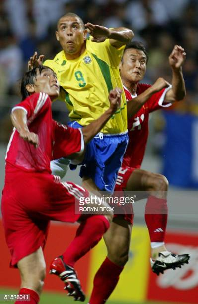 Brazil's Ronaldo goes up for a header between China's Du Wei and Xu Yunlong 08 June 2002 at the Jeju World Cup Stadium in Seogwipo during first round...