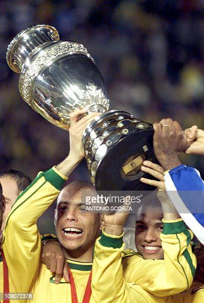 Brazil's Ronaldo hold the the Copa America trophy 18 July as he celebrates with teammate after the team defeated Uruguay 30 in Asuncion AFP PHOTO...