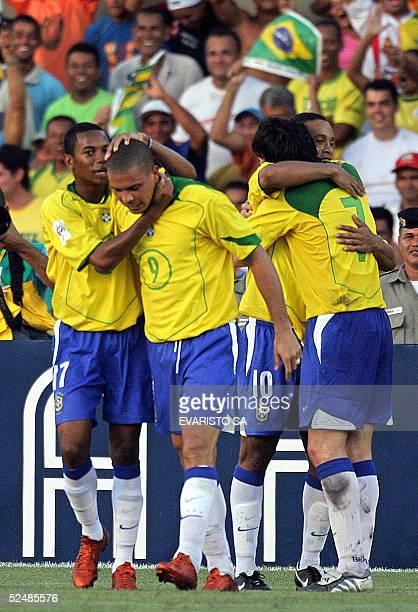 Brazil's Ronaldo Nazario is hugged by Robson de Souza Robinho while Ricardo Leite Kaka celebrates his goal with Ronaldinho Gaucho 27 March 2005...