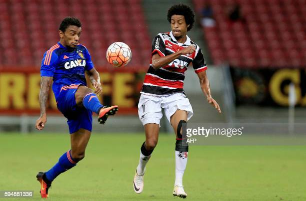 Brazil's Santa Cruz player Derley vies for the ball with Brazil Sport Recife Paulo Roberto during their Copa Sudamericana match at Arena Pernambuco...
