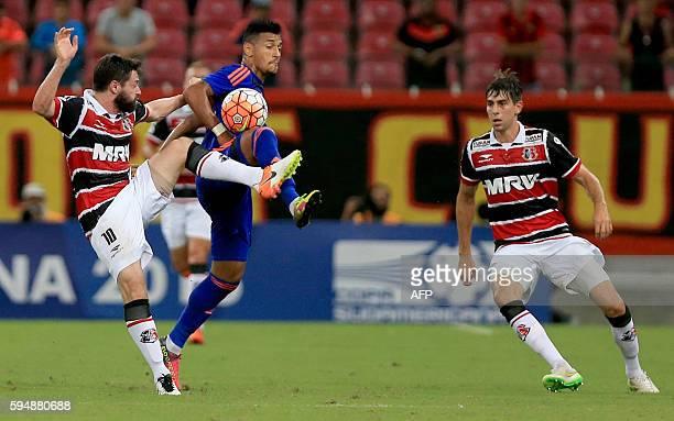 Brazil's Santa Cruz player Joao Paulo vies for the ball with Brazil Sport Recife Rogerio during their Copa Sudamericana match at Arena Pernambuco...