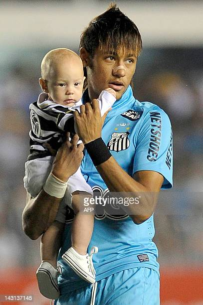 Brazil's Santos FC player Neymar holds his son Davi Lucca before the start of their 2012 Copa Libertadores football match against Bolivia´s The...