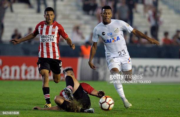 Brazil's Santos forward Arthur Gomes vies for the ball with Argentina's Estudiantes de La Plata defenders Facundo Sanchez and Ivan Gomez during their...