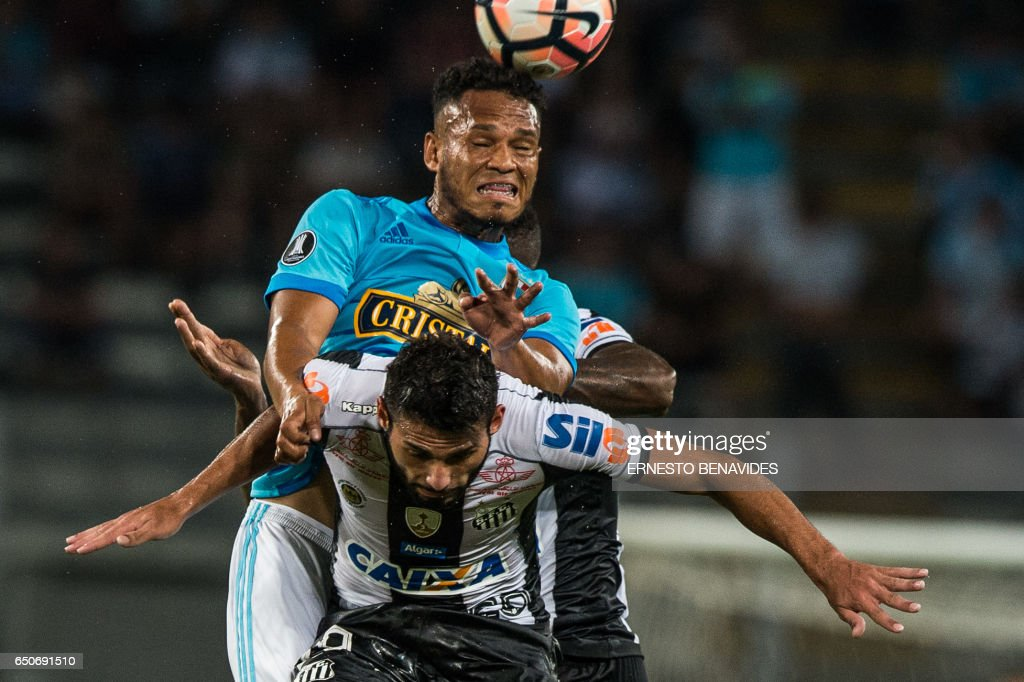 Brazil's Santos player Thiago Maia (front) vies for the ball with Peru's Sporting Cristal player Rolando Blackburn (back) during their Libertadores Cup football match at the National stadium in Lim...