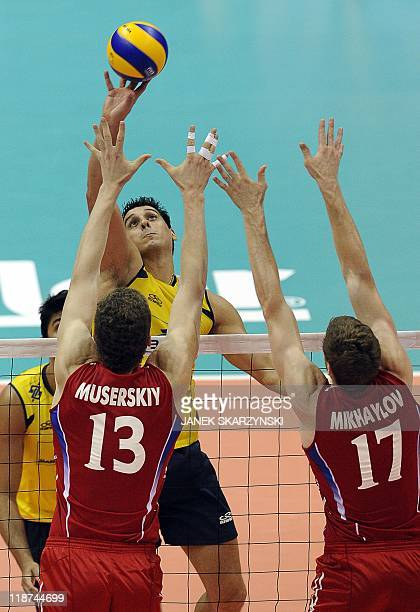 Brazil's Sidnei dos Santos spikes the ball against Russia's Dimitiy Muserskiy and Maxim Mikhalkov during their Volleyball World League gold medal...
