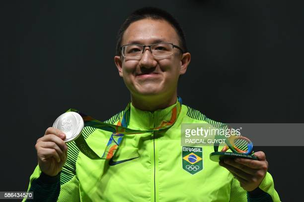 Brazil's silver medallist Felipe Almeida Wu poses on the podium during the medal ceremony for the men's 10m air pistol shooting event at the Rio 2016...