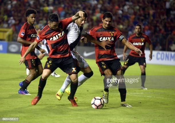 Brazil's Sport Recife players Durval and Eugenio Mena vie for the ball with Uruguay's Danubio player Joaquin Ardaiz during their Copa Sudamericana...