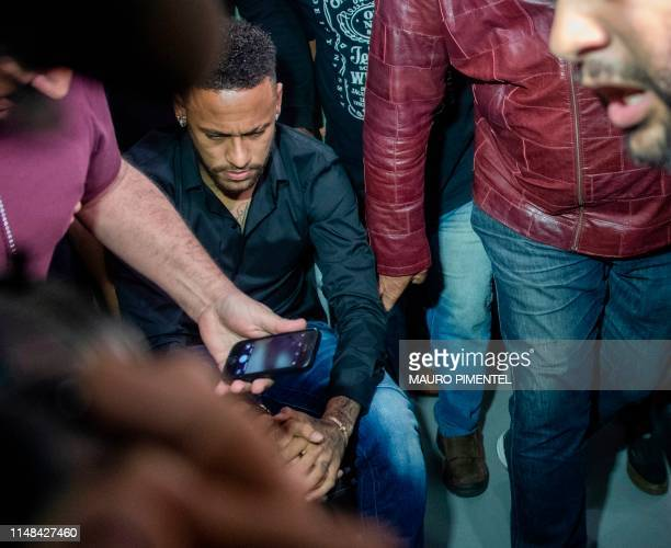 TOPSHOT Brazil's star striker Neymar arrives using a wheelchair to the Police Station to give a statement for posting intimate WhatsApp messages with...