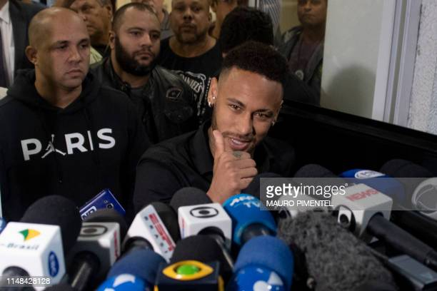 TOPSHOT Brazil's star striker Neymar gives the thumb up as he leaves a Police Station after giving a statement to police for posting intimate...