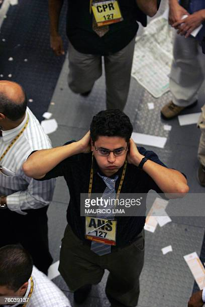 A Brazil's stock trader gestures while he checks the index board prior to the morning closing time at the Mercantile Futures Exchange in Sao Paulo...