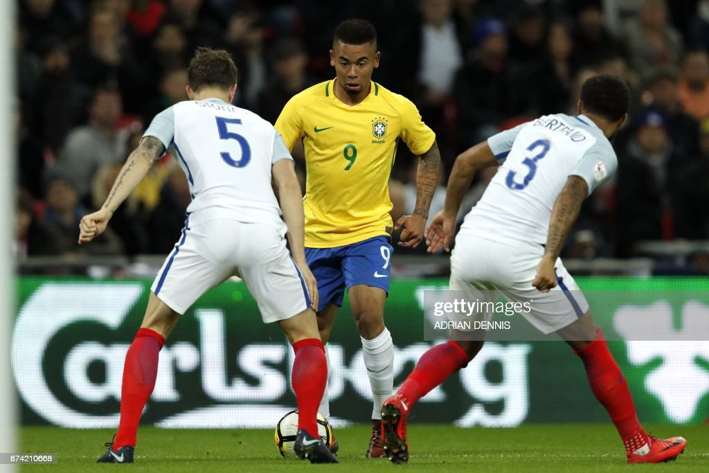 TOPSHOT - Brazil's striker Gabriel Jesus (C) vies with England's defender John Stones (L) and England's defender Ryan Bertrand (R) during the international friendly football match between England and Brazil at Wembley Stadium in London on November 14, 2017. / AFP PHOTO / Adrian DENNIS / NOT