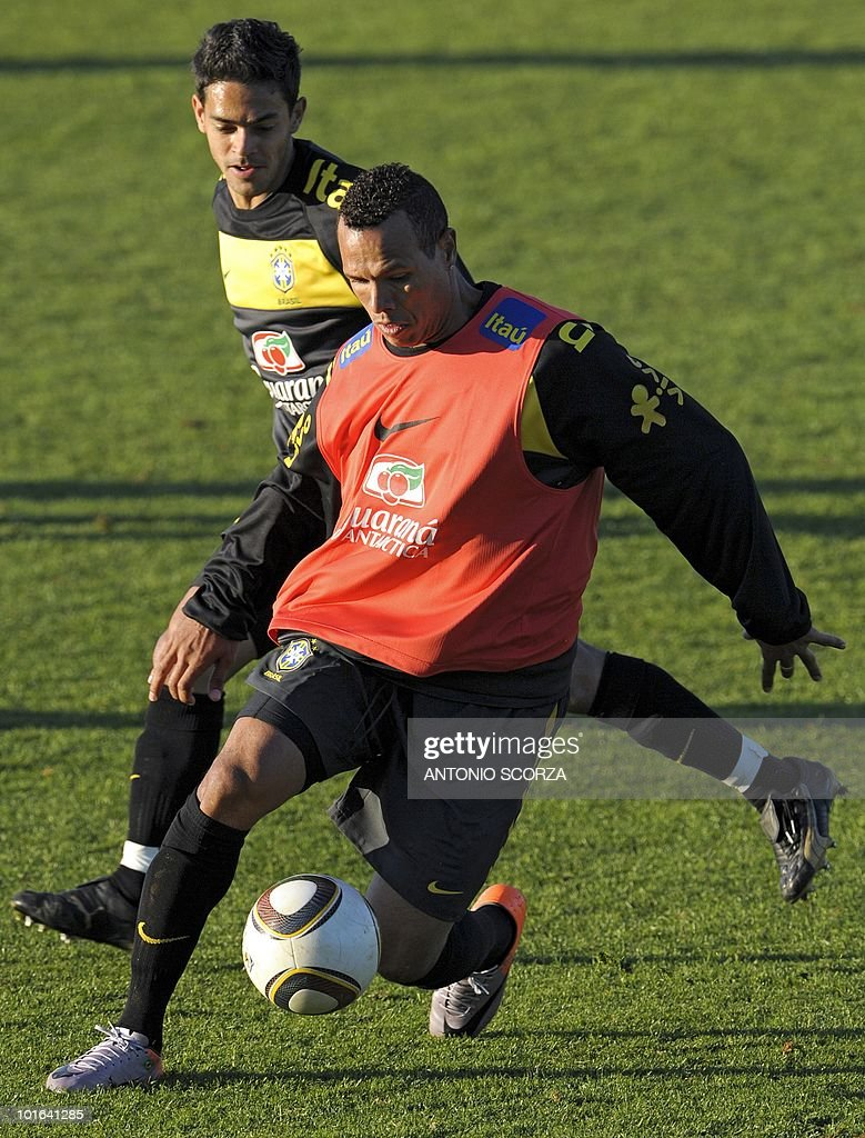 Brazil's striker Luis Fabiano (R) controls the ball as teammate Josue (behind) looks on during a team training session at Randburg High School on June 5, 2010 in Johannesburg. The team is preparing to compete in the 2010 World Cup football tournament in South Africa.