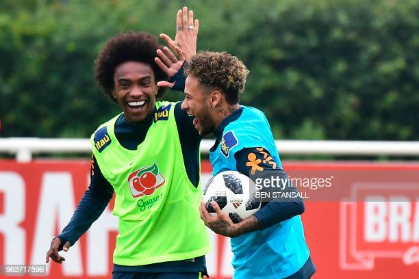 TOPSHOT Brazil's striker Neymar highfives Brazil's midfielder Willian as they take part in a training session at Tottenham Hotspur's Enfield Training...