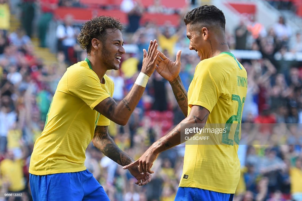 TOPSHOT - Brazil's striker Roberto Firmino (R) celebrates with Brazil's striker Neymar after scoring their second goal during the International friendly football match between Brazil and Croatia at Anfield in Liverpool on June 3, 2018. - Brazil won the game 2-0.