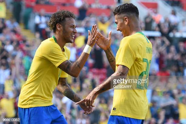 TOPSHOT Brazil's striker Roberto Firmino celebrates with Brazil's striker Neymar after scoring their second goal during the International friendly...