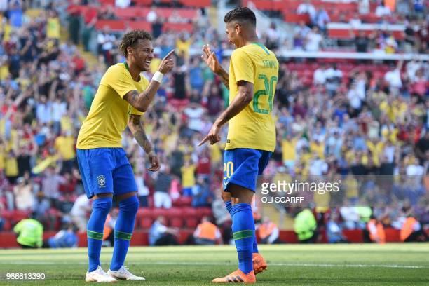 Brazil's striker Roberto Firmino celebrates with Brazil's striker Neymar after scoring their second goal during the International friendly football...